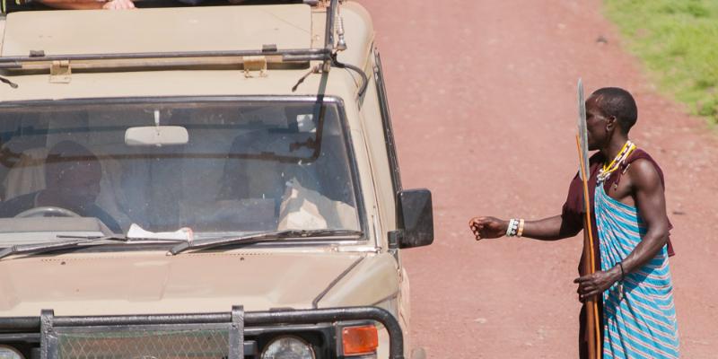 un massaï demande de l'argent à une voiture de safari