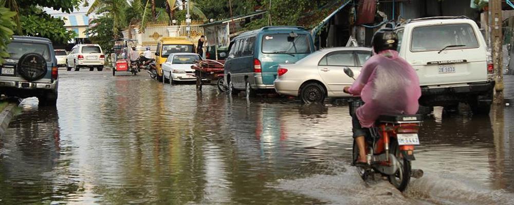 une personne à vélo dans une rue inondée